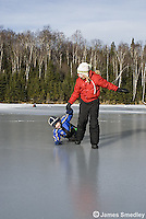Young girl and boy playing on the slippery lake ice