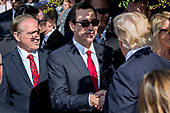 Steven Mnuchin, United States Secretary of the Treasury, center, shakes hands with U.S. President Donald J. Trump during a ceremony to commemorate the September 11, 2001 terrorist attacks, at the Pentagon in Washington, D.C., U.S., on Monday, Sept. 11, 2017. Trump is presiding over his first 9/11 commemoration on the 16th anniversary of the terrorist attacks that killed nearly 3,000 people when hijackers flew commercial airplanes into New York's World Trade Center, the Pentagon and a field near Shanksville, Pennsylvania. Photographer: Andrew Harrer/Bloomberg<br /> Credit: Andrew Harrer / Pool via CNP