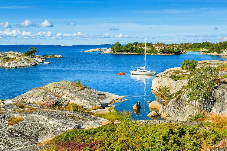 Segelbåt i naturhamn vid kallskär i Stockholms skärgård. / Sailboat in the Stockholm archipelago in Sweden.