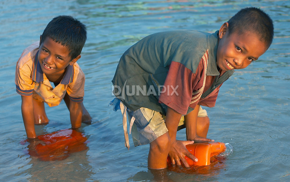 Two young boys collect water, Papagaran island, Komodo National Park