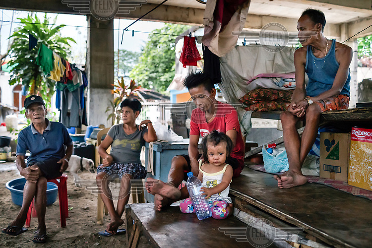 A family gather in the shack they've built over a tomb where they live in Manila North Cemetery.  Manila North Cemetery is home to thousands of 'informal settlers' who have built shacks using in and around the mausoleums, crypts and tombs. In comparison to the city's dangerous shantytowns the cemetery is relatively quiet and safe. However, water must be collected from a few public wells and the electricity supply is erratic, usually stolen from mains cables. In the summer the sweltering heat drives people to sleep outside often on top of the tombs.<br /> <br /> Some of the residents live in the crypts and mausoleums of wealthy families, who pay them a stipend to clean and watch over them. Others make a living carving headstones or selling candles to visitors and helping out at funerals as the daily life of the cemetery goes on around the people who live there.