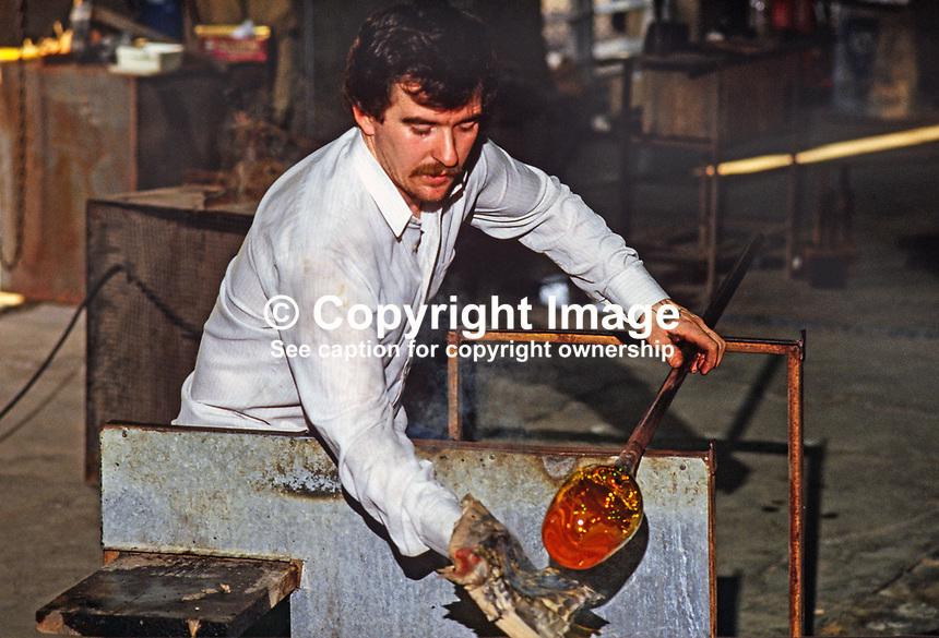 An operative at work &quot;shaping&quot; the molten glass in the Tyrone Crystal factory, Dungannon, N Ireland, UK. 19850001TC3.<br />