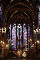Low angle view of the nave and the choir of the upper chapel of La Sainte-Chapelle (The Holy Chapel), 1248, Paris, France. Fifteen huge mid-13th century windows fill the nave and apse of La Sainte-Chapelle which was commissioned by King Louis IX of France to house his collection of Passion Relics, including the Crown of Thorns. The Sainte-Chapelle is considered among the highest achievements of the Rayonnant period of Gothic architecture. Picture by Manuel Cohen