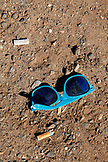 USA, Los Angeles, a broken pair of sunglasses and a cigarette butt in the dirt near Abbot Kinney Boulevard