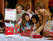 Washington, D.C. - December 22, 2006 -- First lady Laura Bush helps wrap Christmas gifts destined for injured soldiers and their families who are staying at the Mologne House at the Walter Reed Army Medical Center in Washington, D.C. on Friday, December 22, 2006.<br /> Credit: Ron Sachs - Pool via CNP