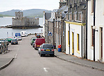 General view of the main shopping street in Castlebay the largest settlement in Barra, Outer Hebrides, Scotland, UK looking to Kisimul castle in the bay