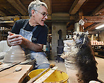 """THE POTTER'S APPRENTICE--Tom Starr throws """"off the hump"""" of clay while giving some attention to his trickster assistant Rosie.  Tom has worked as a potter since the early 1970's.  He is known for his functional stoneware and also his bronze sculptures."""