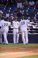 Tampa Yankees designated hitter Michael O'Neill (12) high fives Abiatal Avelino (22) as Santiago Nessy (19) celebrates scoring a run during a game against the Lakeland Flying Tigers on April 8, 2016 at George M. Steinbrenner Field in Tampa, Florida.  Tampa defeated Lakeland 7-1.  (Mike Janes/Four Seam Images)