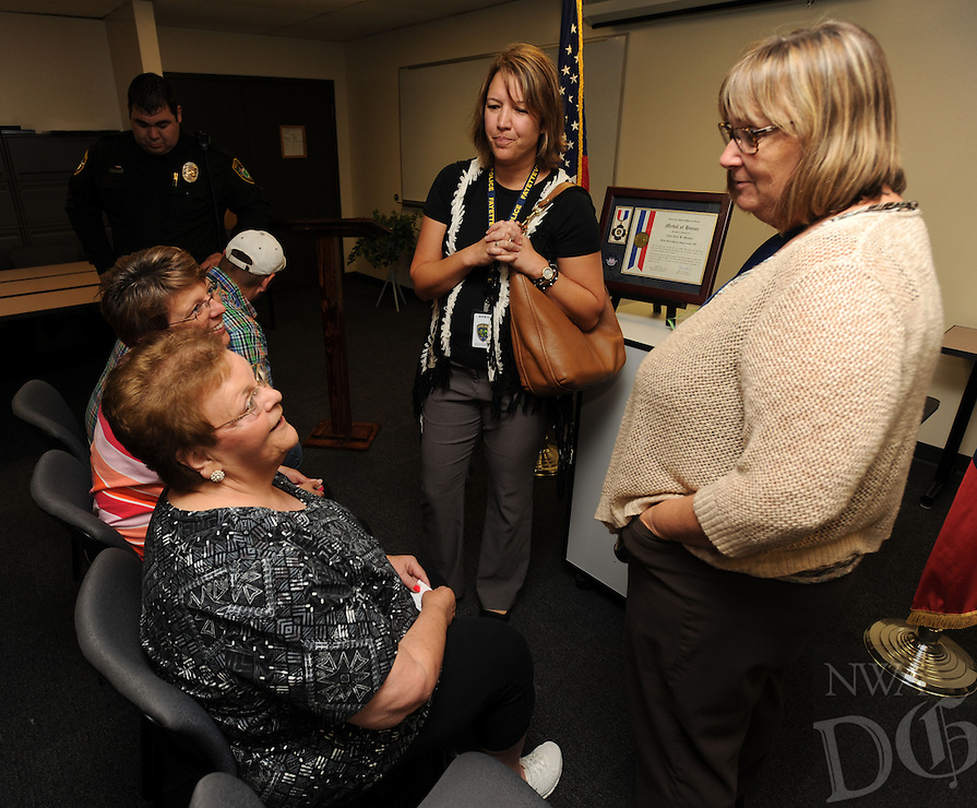 NWA Democrat-Gazette/ANDY SHUPE<br /> Kathy Stocker (right), and Natisha Claypool, (center) both dispatchers with the Fayetteville Police Department, speak Wednesday, Sept. 2, 2015, with Myrrah Mueller (left) of Farmington, and her children Paula Mueller and John Mueller, both of Prairie Grove, during a ceremony to award the Muellers with the American Police Hall of Fame Medal of Honor at the University of Arkansas Police Department in Fayetteville. Myrrah Mueller's husband, West Fork Police Chief Paul Mueller, was shot and killed on March 20, 1981, while making a traffic stop in West Fork following a robbery in Fayetteville. Stocker was a dispatcher with Fayetteville Police Department at the time Paul Mueller was shot.