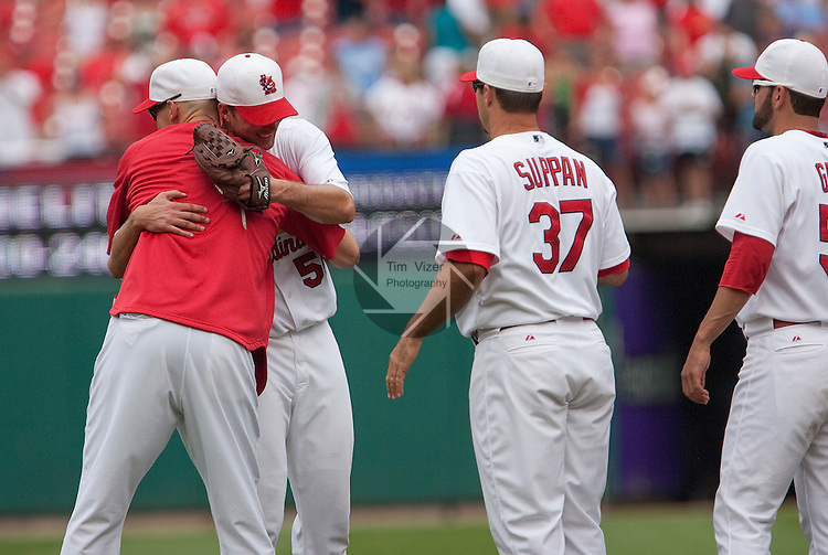 July 4, 2010         St. Louis Cardinals pitcher Chris Carpenter (29, left) hugs St. Louis Cardinals starting pitcher Adam Wainwright (50) after Wainwright pitched a complete game.  Other pitchers are lned up to offer congratulations also.  Both Wainwright and Carpenter were selected to play in the All-Star Game.  The St. Louis Cardinals defeated the Milwaukee Brewers 7-1 in the final game of a four-game homestand at Busch Stadium in downtown St. Louis, MO on Sunday July 4, 2010.