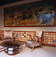 A pair of 50's style armchairs and a glass-topped retro table sit below a giant exhibition poster in the poolside bar