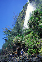 Visitors are shown by Kaluahina Falls, reached from Waipio's black-sand beach.