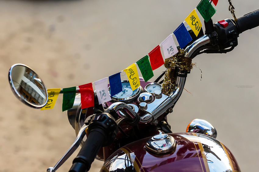 Prayer flags on handlebars of a motorcycle, Old Leh, Ladakh, Jammu and Kashmir State, India.