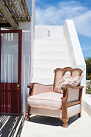 A wooden armchair with red and white striped upholstery on a whitewashed terrace.