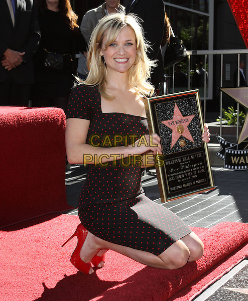 REESE WITHERSPOON.Star on Walk of Fame Ceremony held On the Hollywood Walk of Fame, Hollywood, CA, USA, .1st December 2010..full length kneeling down red shoes black polka dot dress smiling patent frame .CAP/ADM/KB.©Kevan Brooks/AdMedia/Capital Pictures.