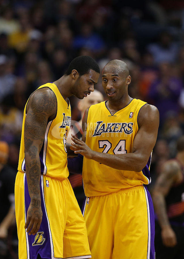 Jan. 30, 2013; Phoenix, AZ, USA: Los Angeles Lakers guard Kobe Bryant (right) talks with teammate Earl Clark in the second half against the Phoenix Suns at the US Airways Center. The Suns defeated the Lakers 92-86.  Mandatory Credit: Mark J. Rebilas-
