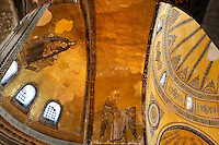 View from below of ceiling inside domes showing mosaic of the Virgin Mary and Jesus (Theotokos and Christ) on the left, Arcangel Gabriel on the right, Hagia Sophia, 532-37, by Isidore of Miletus and Anthemius of Tralles, Istanbul, Turkey. Hagia Sophia, The Church of the Holy Wisdom, has been a  Byzantine church and an Ottoman mosque and is now a museum. The current building, the third on the site, commissioned by Empeor Justinian I, is a very fine example of Byzantine architecture. The historical areas of the city were declared a UNESCO World Heritage Site in 1985. Picture by Manuel Cohen.