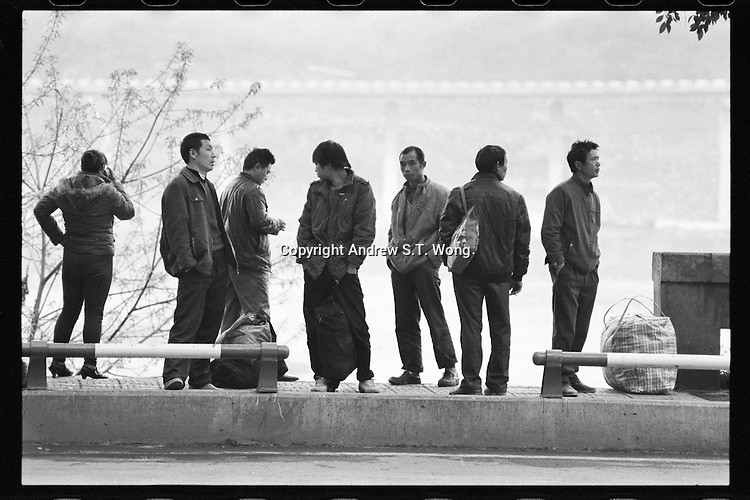 Workers wait for the bus in Chongqing, China's southwestern municipality, in April, 2011.