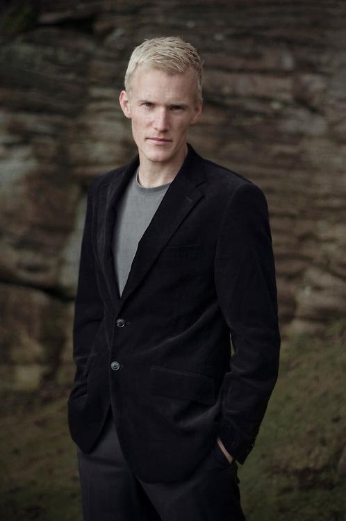 Dark portrait of young man in dark blazer against a stone wall