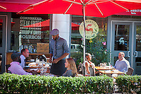 Patrons are served at the outdoor cafe of the Red Rooster restaurant on Lenox Avenue in the neighborhood of Harlem in New York on Friday, September 26, 2014. Wide sidewalks and a renaissance in Harlem have caused a number of restaurants to open catering to the more upwardly mobile newer residents. Lenox Avenue has become Harlem's own restaurant row. (© Richard B. Levine)