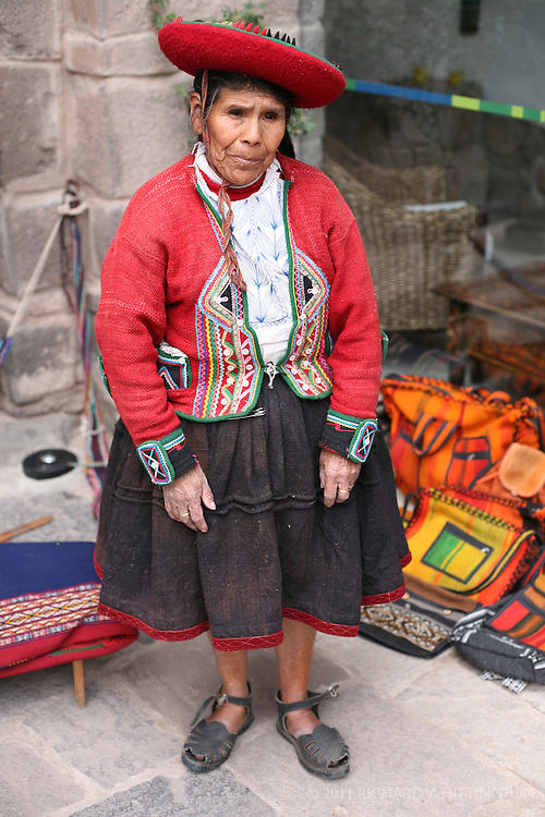 An Indian vendor in Cuzco wears a colorful costume and hat.