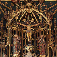 Detail of the crucifixion, from the main altarpiece in the main chapel, in the Old Cathedral of Coimbra, or Se Velha de Coimbra, a 12th century Romanesque Roman Catholic cathedral in Coimbra, Portugal. The altarpiece, 1503, is of gilded and polychrome wood in Gothic style, was commissioned by Bishop Jorge de Almeida and made by the Flemish masters Olivier de Gante and Jean d'Ypres. The cathedral was designed by Master Robert, a French architect, with the works overseen by Master Bernard and Master Soeiro. It was reworked in the 16th century, with the addition of tiled decoration, a portal and Renaissance chapel. The city of Coimbra dates back to Roman times and was the capital of Portugal from 1131 to 1255. Its historic buildings are listed as a UNESCO World Heritage Site. Picture by Manuel Cohen