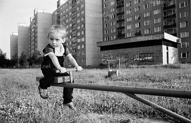 UNGARN, 07.1989.Miskolc-Diosgyor (korrekter: Di--sgy?r).Alltag vor dem Systemwechsel:  Junge auf Spielplatz-Wippe in der riesigen Plattenbausiedlung..Everyday life before the system change:  Boy on the playing ground of the huge prefab block district..© Martin Fejer/EST&OST