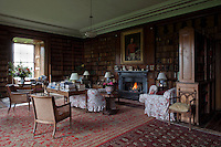 The walls of the library are lined with floor-to-ceiling bookshelves filled with antique leather-bound books