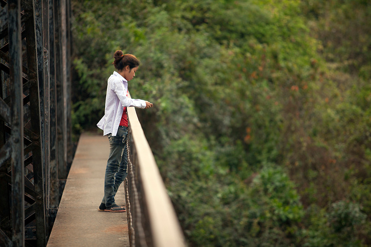 A young woman looks thoughtfully from a bridge near Battambang, Cambodia.  <br /> <br /> Photos &copy; Dennis Drenner 2013.