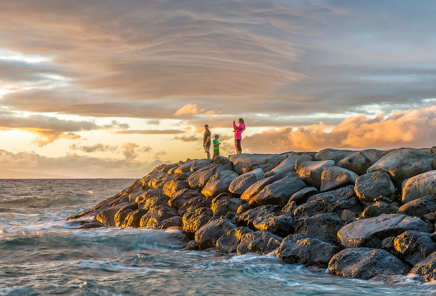 A family group watches the sunset from atop a rocky breakwater at the boat launch at Kamaole Beach Park III, Kihei, Maui, Hawaii.