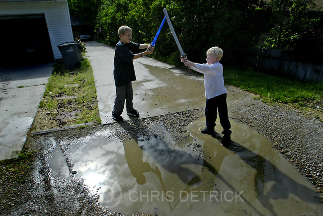 Salt Lake City,Utah--6/12/2005- .**ZONES**.Kyle Cameron, 5, right, and D.J. Rushton, 10, play with plastic swords outside before dinner. The Rushtons gather together every Sunday for a family dinner.    .Photo By: Chris Detrick /Salt Lake Tribune.