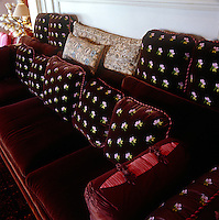 The deep burgundy velvet upholstery of this sofa is enhanced by the collection of scatter cushions