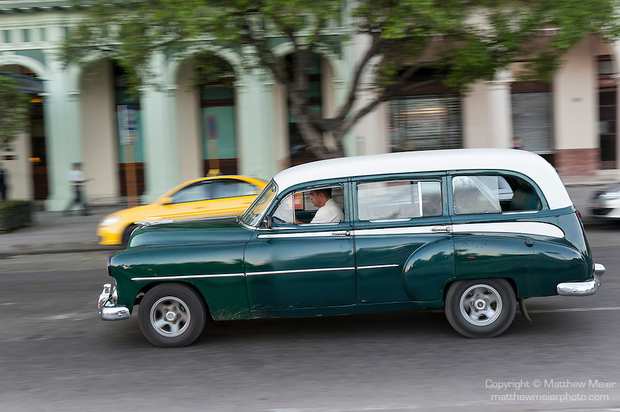 Havana, Cuba; a classic green and white 1952 Chevy station wagon driving along the Paseo de Marti past the Saratoga Hotel
