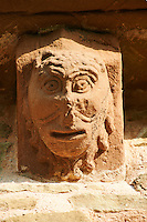 Norman Romanesque exterior corbel no 3 - sculpture of a head, half man half lion. The wide mouth is the same style as theatrical masks. The Norman Romanesque Church of St Mary and St David, Kilpeck Herefordshire, England. Built around 1140