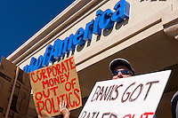 "A man wearing sunglasses holds a sign in front of a Bank of America in Irvine, CA during the Saturday November 5 Occupy Orange County, Irvine march.  Signs read ""Corporate Money out of Politics"" and ""Banks got Bailed Out""."