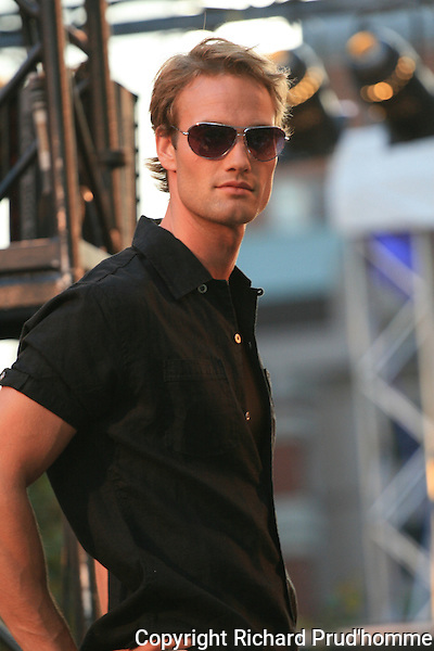 A male model posing for pictures during the  Le chateau fashion show  during  the Mode & Design festival in Montreal