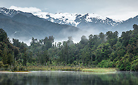 Moody views of Southern Alps near Franz Josef Glacier viewed from Lake Mapourika, Westland Tai Poutini National Park, West Coast, South Westland, UNESCO World Heritage Area, New Zealand, NZ