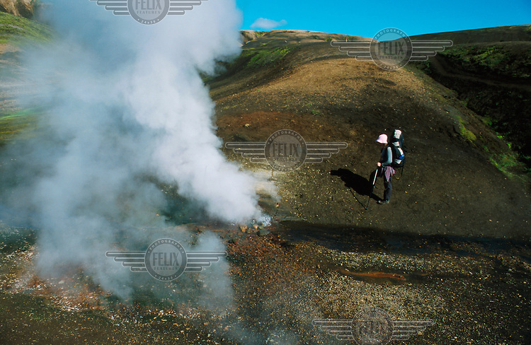 A hiker watches steam rising from a fumarole on the trekking route between Landmannalaugar, Thorsmork and Skogar.