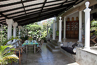 The lush garden surrounds the veranda built in colonial style