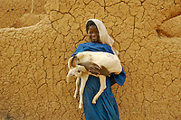 A girl holds a goat as she stands in front of a wall in the village of Intedeyne. /Felix Features