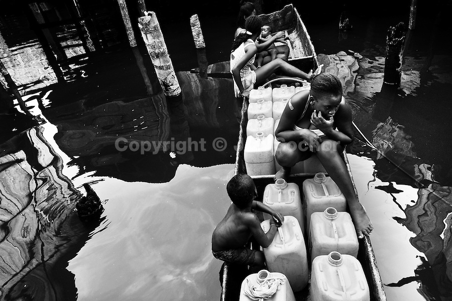 A displaced family carry barrels with drinking water in their canoe inside the stilt house area in Tumaco, Nariño dept., Colombia, 17 June 2010. With nearly fifty years of armed conflict, Colombia has the highest number of civil war refugees in the world. During the last ten years of the civil war more than 3 million people have been forced to abandon their lands and to leave their homes due to the violence. Internally displaced people (IDPs) come from remote rural areas, where most of the clashes between leftist guerrillas FARC-ELN, right-wing paramilitary groups and government forces takes place. Displaced persons flee in a hurry, carrying just personal belongings, and thus they inevitably end up in large slums of the big cities, with no hope for the future.