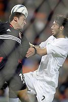 D.C. United's Alecko Eskandarian and Clint Dempsey of the Revolution go for a header as seen through the net. DC United defeated the New England Revolution 4 to 3 in a shoot out after overtime ended in a 3 all tie during the MLS Eastern Conference Championship at RFK Stadium, Washington, D.C., on Saturday, November 6, 2004..