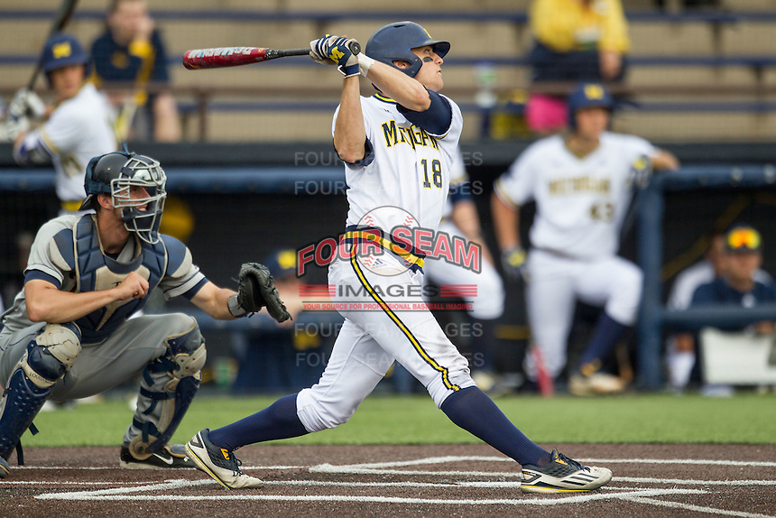 Michigan Wolverines third baseman Jake Bivens (18) follows through on his swing against the Toledo Rockets on April 20, 2016 at Ray Fisher Stadium in Ann Arbor, Michigan. Michigan defeated Bowling Green 2-1. (Andrew Woolley/Four Seam Images)