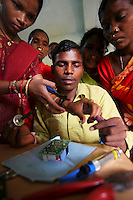 20 year old Meenakshi Diwan (left), and the three other barefoot solar engineers, teach 20 year old Rohim Miniaka (centre) the basics of solar power in an electical workshop in Tinginapu village. The Orissa Tribal Empowerment and Livelihoods Programme (OTELP) is an organisation funded by DFID (Department for International Development) and run with the state government of Orissa. The Orissa Tribal Women's Barefoot Solar Engineers Association has now got a contract to build 3,000 solar-powered lanterns for schools and other institutions and is training other people in the community.