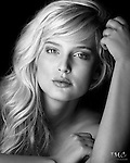 Black & White closeup of beautiful young blonde model with brown eyes, posed against black background