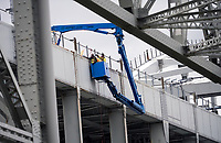 Three workers maintain and repair the nuts and bo;lets of the original Blue Water Bridge.