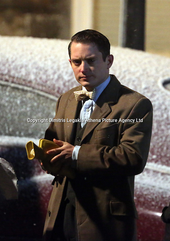 Pictured: Elijah Wood warms up his hands with a hot water bottle. Tuesday 11 February 2014<br /> Re: A Swansea street was transformed into 1950s New York for new Dylan Thomas biopic 'Set Fire to the Stars' starring Holywood actor Elijah Wood.<br /> Gloucester Place in Swansea Marina was used to film a snowy scene in New York.<br /> Half a dozen 50s American cars were used for the scene played by Elijah Wood and Celyn Jones.<br /> The new movie will explore the fractious relationship between Dylan Thomas played by Jones and John Malcolm Brinnin played by WOod, who brought the Welshman to the USA and acted as his tour agent.