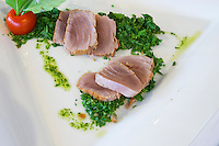 Fresh grilled tuna fish on a bed of herbs from the luxury Excelsior Hotel and Spa restaurant terrace Dubrovnik, old city. Dalmatian Coast, Croatia, Europe.