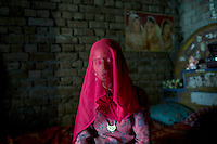 A Babaria woman with her head covered by a pink headscarf sits in her house. The Babaria are a major source of illegally traded tiger parts since they used to hunt them when it was legal to do so and now sell them to traffickers.