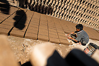 Brian, a ten-year-old Salvadoran boy, molds bricks of clay at a brick factory in Istahua, El Salvador, 21 December 2013. Child labour is a common practice at the artisanal brick factories, found mainly in rural areas of El Salvador. Poverty and insufficient earnings in agriculture force parents to employ their own children, in an effort to ensure the livelihood for the whole family. Children aged 8-10 are allowed to work slower, with smaller volumes of clay, while children aged 12 and up work regularly, 8-10 hours a day, 6 days a week.